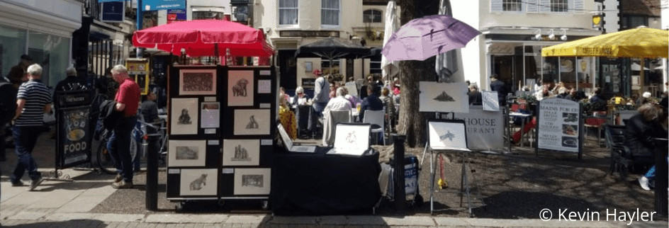 Brighton Market stall in Brighton on a busy summers day displaying pencil wildlife art